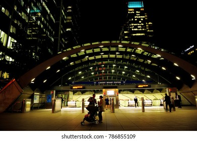 LONDON, ENGLAND-25 SEPTEMBER 2013: People in front of modern entrance to Jubilee line at Canary Wharf station and modern high buildings at night in Canary Wharf, Docklands, London, England, UK