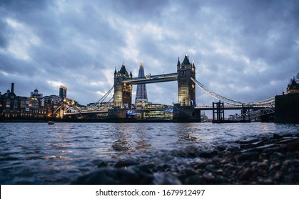London evening cityscape with Tower Bridge and the Shard. Low wide angle view with reflection in the river.