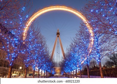 London Eye at twilight and blue lighting decoration on trees. At a height of 135m, it is the tallest Ferris wheel in Europe.