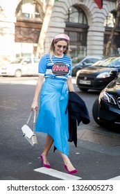 LONDON - FEBRUARY 15, 2019:  A blond guest wears a pink headband, a Miu Miu blue t-shirt, a blue skirt, red shoes during London Fashion Week
