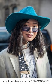 LONDON - FEBRUARY 15, 2019: Fashion blogger Wenwen Stokes wears a Louis Vuitton T shirt and scarf, Topshop suit, Miu Miu sunglasses, Dover Street Market hat during London Fashion Week February