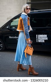 LONDON - FEBRUARY 15, 2019: A guest wears a blue and orange aviator jacket with sheep wool inner lining, a blue skirt, an orange bag, leather boots, a pink top, sunglasses, during London Fashion Week