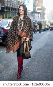 LONDON - FEBRUARY 15, 2019: Nurce Erben wears sunglasses, a Fendi logo poncho, a necklace, a Fendi bag, red high leather boots, during London Fashion Week February
