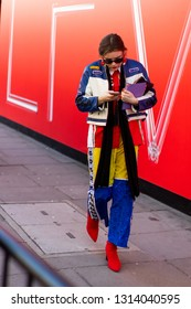 LONDON - FEBRUARY 15, 2019: Stylish attendees arriving at 180 The Strand for London Fashion Week wearing personalised overcoats.