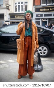 LONDON - FEBRUARY 15, 2019: Stylish attendees gathering outside 180 Strand for London Fashion Week. The girl in the green beret, brown fur coat from faux fur and flared trousers