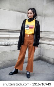 LONDON - FEBRUARY 15, 2019: Stylish attendees gathering outside 180 The Strand for London Fashion Week. Girl in brown flared trousers, blazer, and yellow sweatshirt