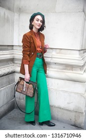 LONDON - FEBRUARY 15, 2019: Stylish attendees gathering outside 180 The Strand for London Fashion Week. Girl in green flared trousers and a brown jacket
