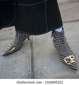 LONDON - FEBRUARY 15, 2019: Stylish attendees gathering outside 180 The Strand for London Fashion Week. Fragment of legs with women shoes BALENCIAGA BB