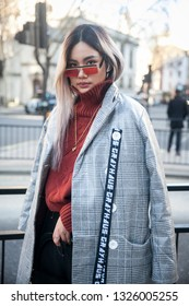 LONDON - FEBRUARY 15, 2019: Stylish attendees gathering outside 180 Strand for London Fashion Week. Girl in sunglasses black wide trousers, brown turtleneck and black and white checkered coat