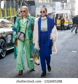 LONDON - FEBRUARY 15, 2019: Stylish attendees gathering outside 180 The Strand for London Fashion Week. A blond girl wears sunglasses in green coat and suit