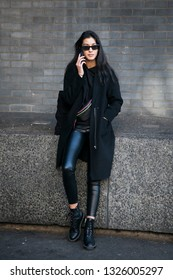 LONDON - FEBRUARY 15, 2019: Stylish attendees gathering outside 180 Strand for London Fashion Week. The girl in black coat and leather pants in tight-fitting talking on phone