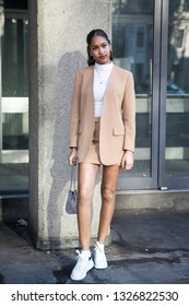 LONDON - FEBRUARY 15, 2019: Stylish attendees gathering outside 180 The Strand for London Fashion Week. Girl in a beige jacket and short skirt