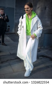 LONDON - FEBRUARY 15, 2019: Stylish attendees gathering outside 180 The Strand for London Fashion Week. Girl in a white sports coat and green hoodie
