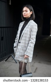 LONDON - FEBRUARY 15, 2019: Stylish attendees gathering outside 180 The Strand for London Fashion Week. Girl in beige checkered jacket and short skirt