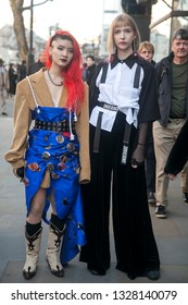 LONDON - FEBRUARY 15, 2019: Stylish attendees gathering outside 180 Strand for London Fashion Week. Girl with crimson hair in jacket and blue high skirt with badges with friend in white shirt and blac