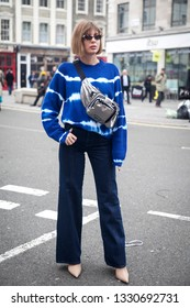 LONDON - FEBRUARY 15, 2019: Stylish attendees gathering outside 180 The Strand for London Fashion Week. Girl in flared jeans and a blue and white sweater with a silver belt bag