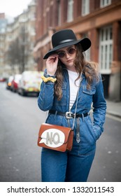 "LONDON - FEBRUARY 15, 2019: Stylish attendees gathering outside 180 The Strand for London Fashion Week. girl in blue denim jumpsuit and wide-brimmed hat with small bag with sign ""No"""