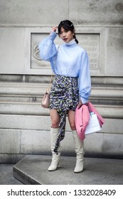 LONDON - FEBRUARY 15, 2019: Stylish attendees gathering outside 180 The Strand for London Fashion Week. A girl in a blue chiffon blouse, a colorful skirt in flowers and a pink jacket