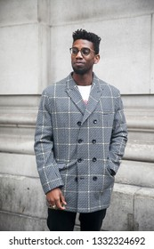 LONDON - FEBRUARY 15, 2019: Stylish attendees gathering outside 180 The Strand for London Fashion Week. A man with a short haircut in a gray checkered jacket and white t-shirt