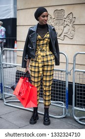 LONDON - FEBRUARY 15, 2019: Stylish attendees gathering outside 180 The Strand for London Fashion Week. Girl in a black leather jacket and checkered yellow jumpsuit
