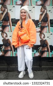 LONDON - FEBRUARY 15, 2019: Stylish attendees gathering outside 180 The Strand for London Fashion Week. The girl wears an orange jacket. Pilot, white sports pants and a knitted hat.