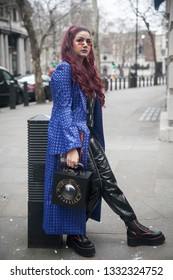 LONDON - FEBRUARY 15, 2019: Stylish attendees gathering outside 180 The Strand for London Fashion Week. Woman wears blue leatherette cloak and black pants. Bag with convex mirror with sign Starsica