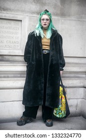 LONDON - FEBRUARY 15, 2019: Stylish attendees gathering outside 180 The Strand for London Fashion Week. Girl with green hair in a fur coat and black velor flared pants