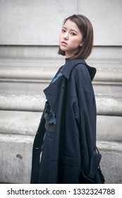 LONDON - FEBRUARY 15, 2019: Stylish attendees gathering outside 180 The Strand for London Fashion Week. Girl in black short culottes, cloak and blouse with slits