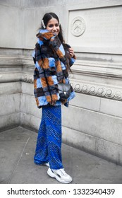 LONDON - FEBRUARY 15, 2019: Stylish attendees gathering outside 180 The Strand for London Fashion Week. Girl wears striped fur coat made of faux fur, blue wide trousers with silver rivets
