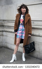 LONDON - FEBRUARY 15, 2019: Stylish attendees gathering outside 180 The Strand for London Fashion Week. girl wears brown faux fur coat, plaid mini skirt, white t-shirt and leather jacket.