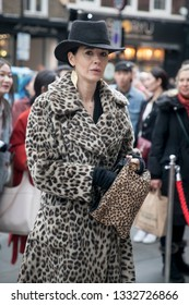 LONDON - FEBRUARY 15, 2019: Stylish attendees gathering outside 180 The Strand for London Fashion Week. Woman in leopard coat and black hat