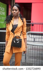 LONDON - FEBRUARY 15, 2019: Stylish attendees gathering outside 180 The Strand for London Fashion Week. Girl in an orange trouser suit and black top