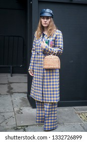 LONDON - FEBRUARY 15, 2019: Stylish attendees gathering outside 180 The Strand for London Fashion Week. Girl wears a checkered blue and beige coat and flared trousers and cap with wicker small bag.