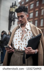 LONDON - FEBRUARY 15, 2019: Stylish attendees gathering outside 180 The Strand for London Fashion Week. The man is wearing a white shirt in cubes, a beige coat and gray checkered pants.