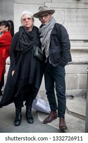 LONDON - FEBRUARY 15, 2019: Stylish attendees gathering outside 180 The Strand for London Fashion Week. Woman with dyed white hair in a long black cardigan poses with a man in a high gray hat