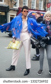 LONDON - FEBRUARY 15, 2019: Stylish attendees gathering outside 180 The Strand for London Fashion Week. Short hair girl wears white pants, shirt and blue jacket with a fringe