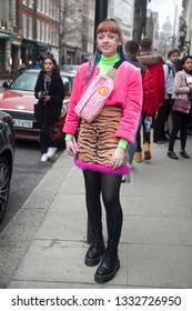 LONDON - FEBRUARY 15, 2019: Stylish attendees gathering outside 180 The Strand for London Fashion Week. Girl wears pink terry jacket, mini skirt with zebra pattern and multi-colored man purse.