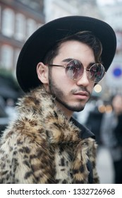 LONDON - FEBRUARY 15, 2019: Stylish attendees gathering outside 180 The Strand for London Fashion Week. man in a leopard faux fur coat and wide-brimmed hat