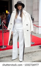 LONDON - FEBRUARY 15, 2019: Stylish attendees gathering outside 180 The Strand for London Fashion Week. Girl in a white coat, pantsuit and brown hat