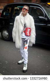 LONDON - FEBRUARY 15, 2019: Stylish attendees gathering outside 180 The Strand for London Fashion Week. girl with braids in white woolly fur coat made of faux fur, tracksuit and a red belt bag Suprem