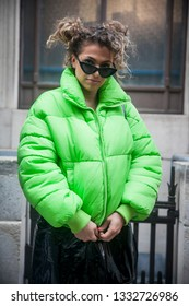 LONDON - FEBRUARY 15, 2019: Stylish attendees gathering outside 180 The Strand for London Fashion Week. curly girl in a green jacket puffer