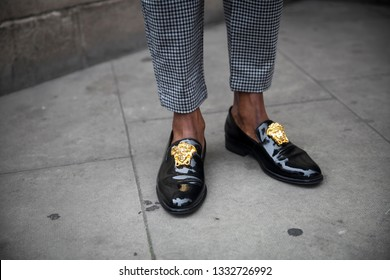 LONDON - FEBRUARY 15, 2019: Stylish attendees gathering outside 180 The Strand for London Fashion Week. fragment of legs in gray trousers, black patent leather shoes with gold buckle