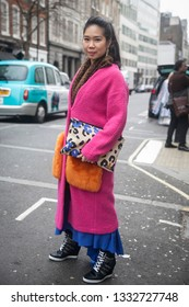 LONDON - FEBRUARY 15, 2019: Stylish attendees gathering outside 180 Strand for London Fashion Week. A girl wears pink coat and blue Girl with dreadlocks in a gray plaid coat and dress with a culotte