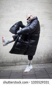 LONDON - FEBRUARY 17, 2019: London Fashion Week. Blonde man wears clear pvc belt bag, black down jacket and grey trousers, white sneakers with Saunt Lauren bag
