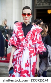 LONDON - FEBRUARY 17, 2019: Stylish attendees gathering outside 180 The Strand for London Fashion Week.  guest is seen outside London Fashion Week in a red and white wrap dress and sparkly heels