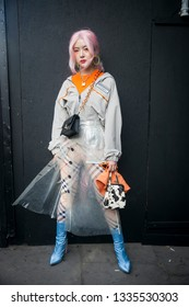 LONDON - FEBRUARY 17, 2019: Stylish attendees gather outside 180 Strand for London Fashion Week. Girl wears plastic transparent rain coat with orange sweater , cow print handbag with baby blue heels