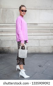 LONDON - FEBRUARY 17, 2019: Stylish attendees gathering outside 180 The Strand for London Fashion Week. Girl in a lilac sweater and brown skirt with a leopard print