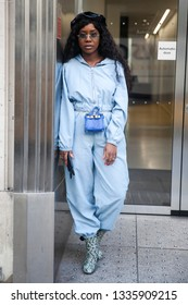 LONDON - FEBRUARY 17, 2019: Stylish attendees gathering outside 180 The Strand for London Fashion Week. The girl is dressed in a blue jumpsuit with an animal print, with baby bag