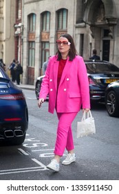 LONDON - FEBRUARY 17, 2019: Stylish attendees gathering outside 180 The Strand for London Fashion Week. Girl in a crimson double-breasted jacket and narrow pants cigarette