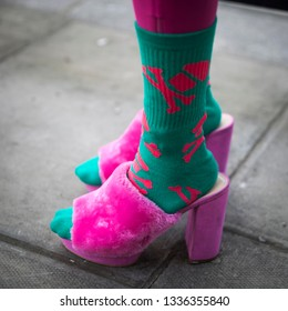 LONDON - FEBRUARY 17, 2019: Stylish attendees gathering outside 180 The Strand for London Fashion Week. Fragment: green terry socks, pink shaggy fluffy shoes